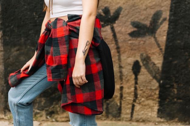 Mujer con tatuaje de flores en su mano de pie delante de la pared
