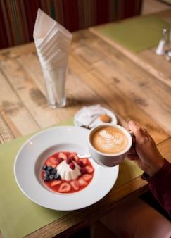 Mujer con taza de café y blanco pudin cremoso lechoso con mermelada y bayas