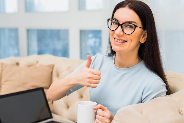 Mujer con la taza de café que muestra el pulgar hacia arriba