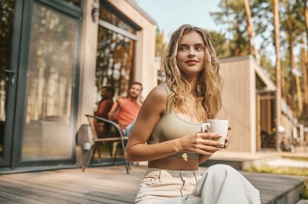 Mujer con taza sentada en el porche de la casa