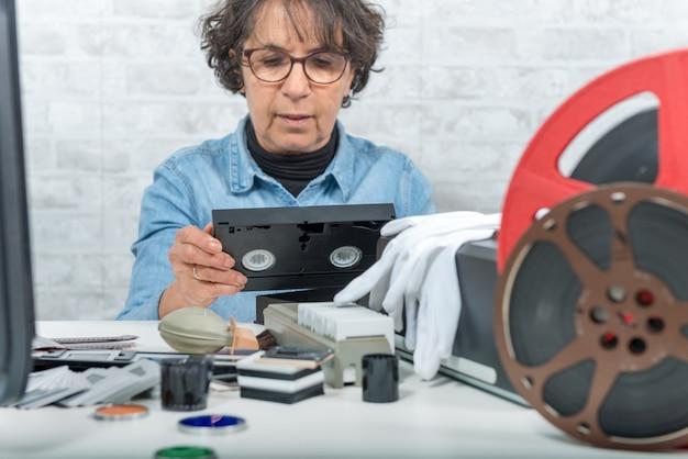 Mujer técnica con casete vhs para digitalización