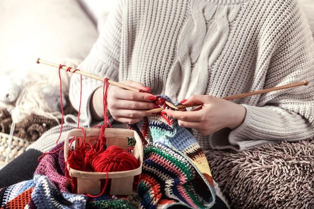 Mujer teje agujas de tejer en el sofá