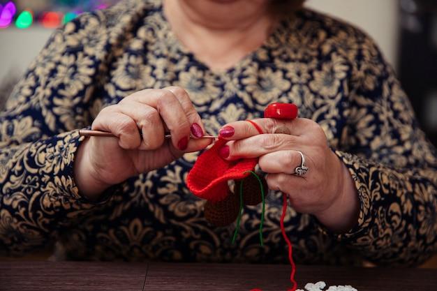 Mujer tejiendo con hilos rojos. foto de alta calidad