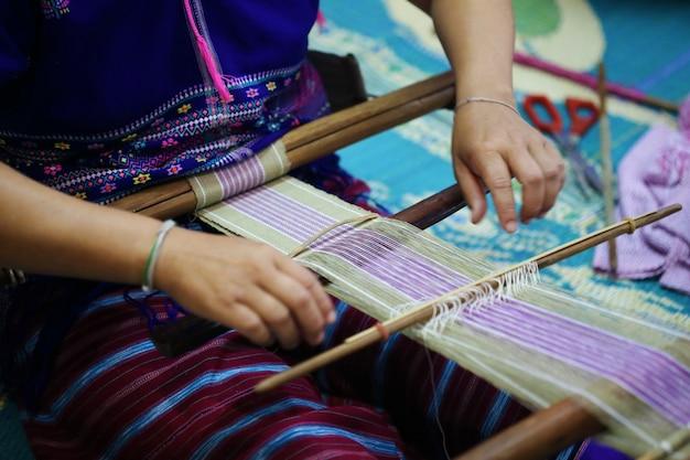 Mujer tejiendo patrón azul y blanco en telar, cultura de tribu de colina, chiang mai
