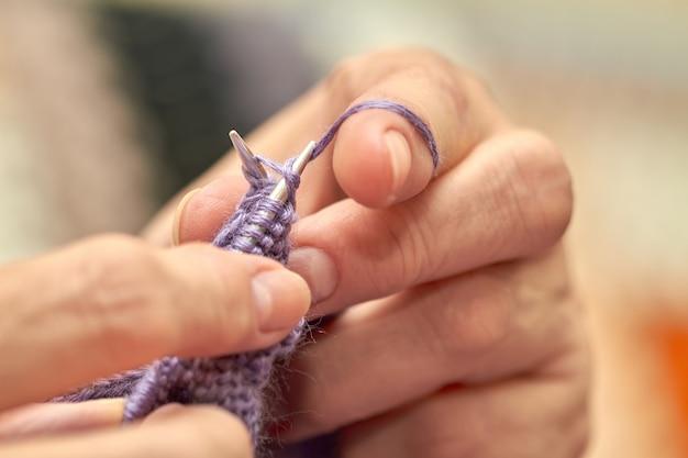 La mujer está tejiendo un suéter azul cálido. un hobby de anciana está tejiendo.
