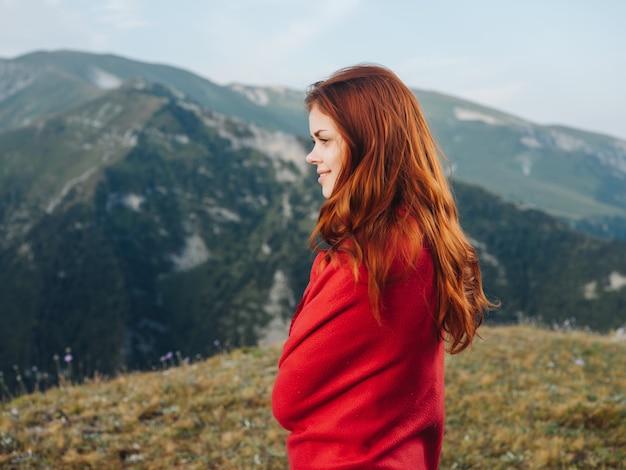 Mujer en una tela escocesa roja en las montañas al aire libre, aire fresco fresco