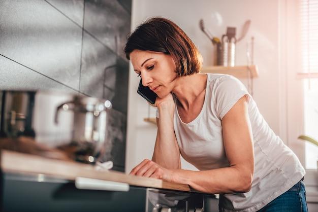 Mujer con teléfono inteligente en la cocina