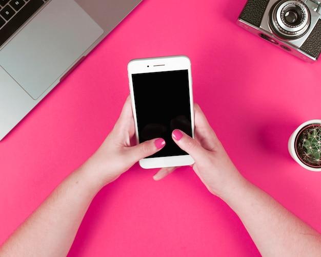 Mujer con teléfono inteligente con ordenador portátil; cámara y planta en maceta sobre fondo rosa