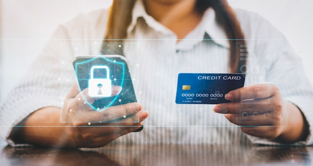 Mujer con teléfono inteligente y tarjeta de crédito con el icono de candado en pantalla digital