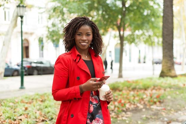 Mujer con teléfono inteligente y vaso de papel sonriendo