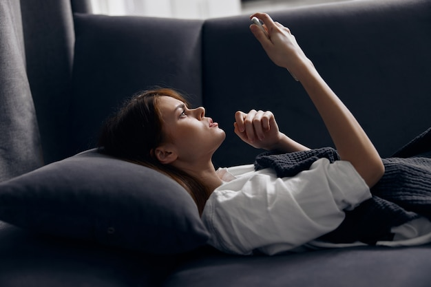 Mujer con teléfono móvil acostado en el sofá en el interior.