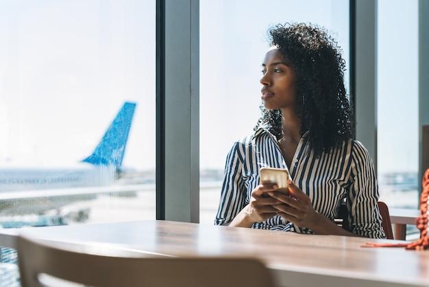 Mujer en el teléfono móvil esperando su vuelo en el aeropuerto
