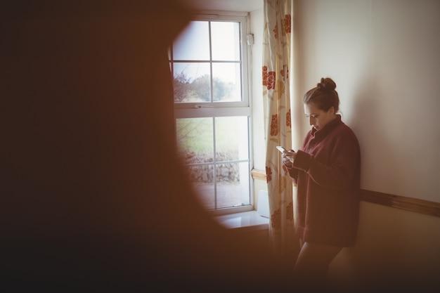 Mujer con teléfono móvil junto a la ventana en casa