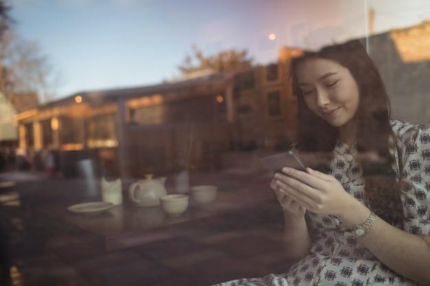 Mujer con teléfono móvil junto a la ventana