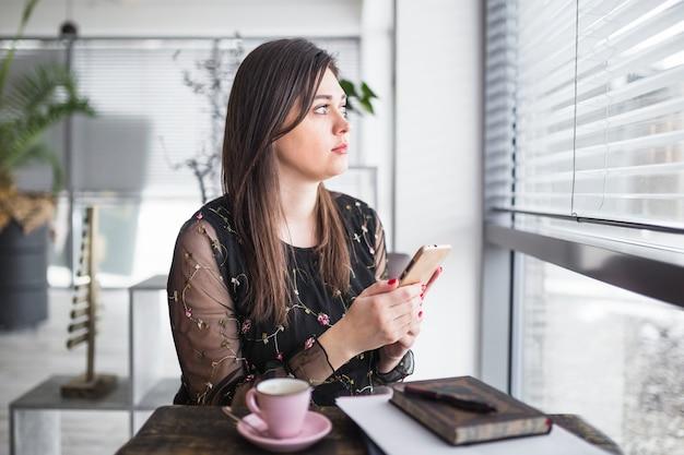 Mujer con teléfono móvil mirando por la ventana en la cafetería