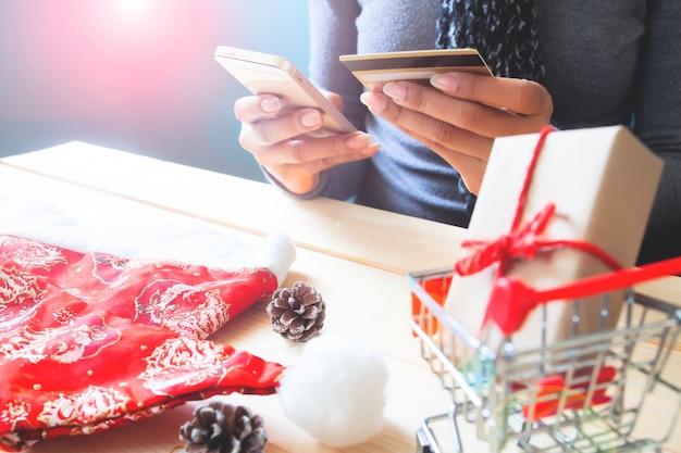 Mujer con teléfono móvil y tarjeta de crédito. compras de navidad en linea