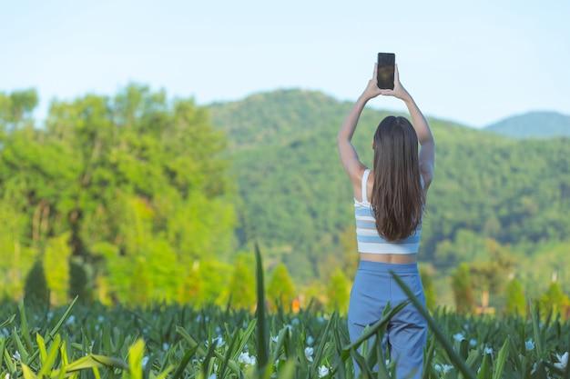 Mujer con teléfono móvil para tomar fotos en el jardín de flores.