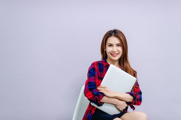 La mujer y el teléfono con pantalla blanca colocan el espacio y tienen una computadora lista para trabajar todo el tiempo.