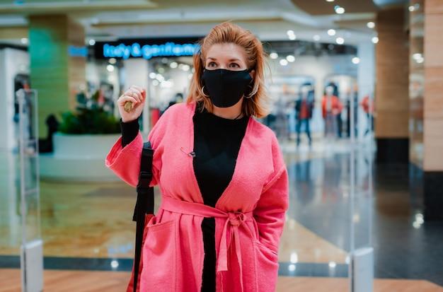 Mujer con teléfono rosa brillante centro comercial abrigo con máscara protectora negra en la cara del aire infectado con virus.