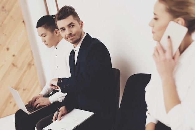Mujer con teléfono está sentado con compañeros de trabajo.