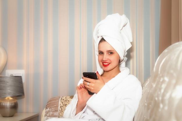 Mujer con teléfono en el sofá de la habitación del hotel después de la ducha