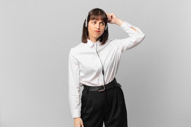Mujer de telemercadeo que se siente perpleja y confundida, rascándose la cabeza y mirando hacia un lado
