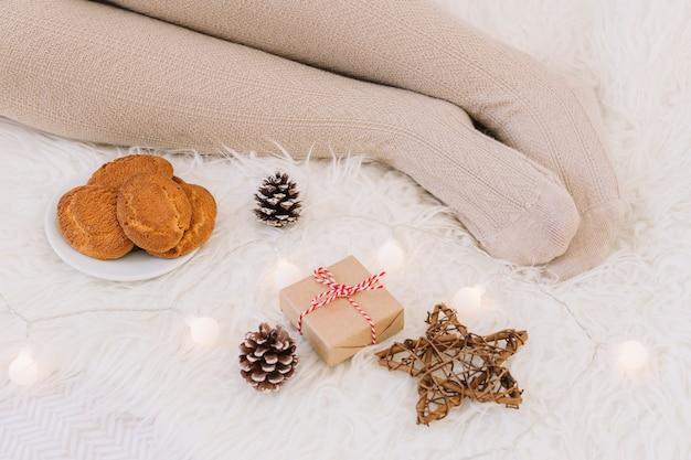 Mujer tendida en la cama con caja de regalo