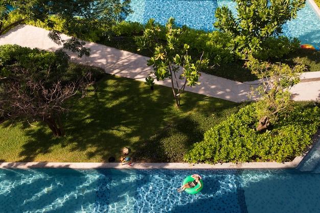 Mujer tendida en globo en la piscina