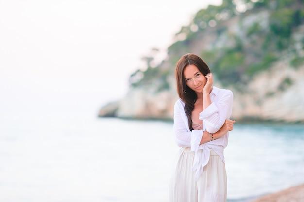 Mujer tendida en la playa disfrutando de las vacaciones de verano