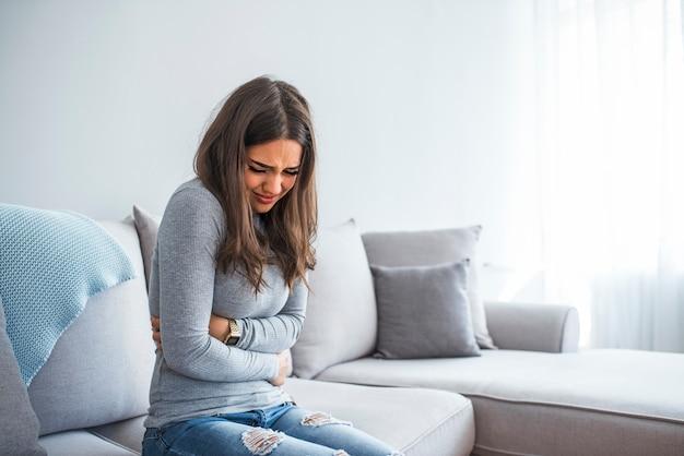 Mujer tendida en el sofá mirando enferma en la sala de estar