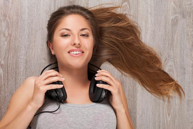 Mujer tendida en el suelo con auriculares
