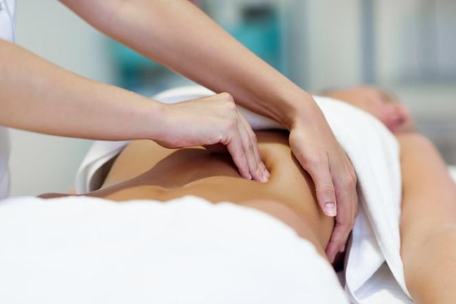 Mujer, teniendo, abdomen, masaje, profesional, osteopatía, terapeuta