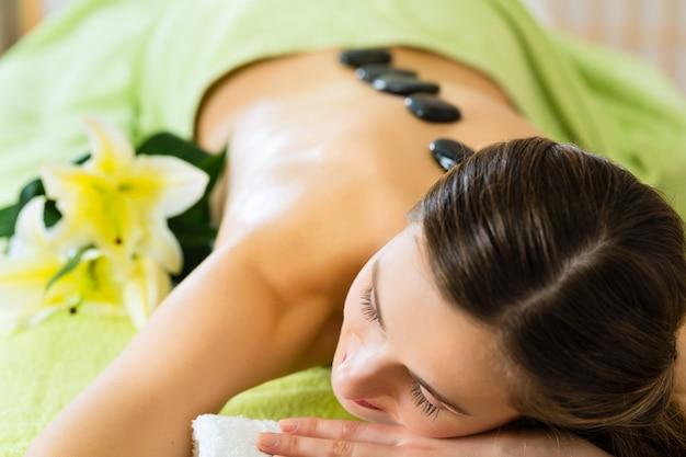 Mujer teniendo bienestar masaje con piedras calientes