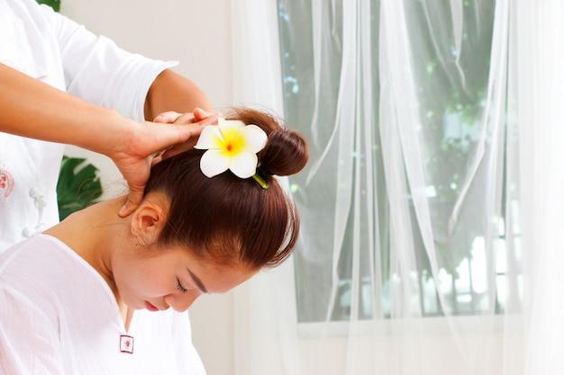 Mujer está teniendo masaje de cuello en estilo tailandés