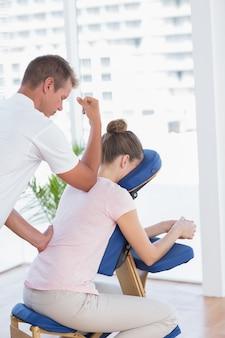 Mujer teniendo masaje de espalda en consultorio médico