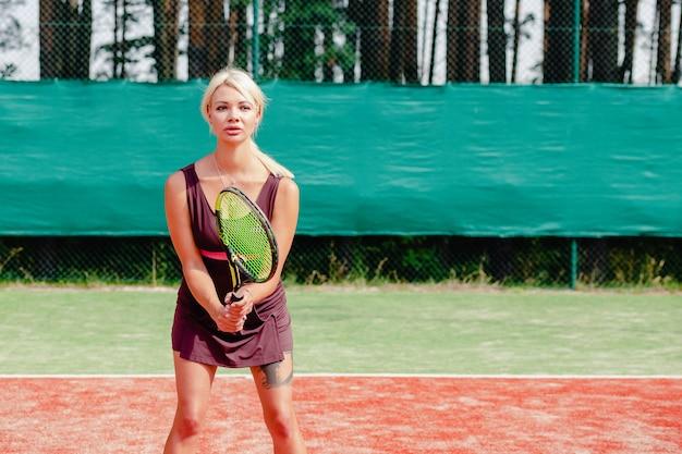 Mujer tenista profesional enfocada en posición lista.