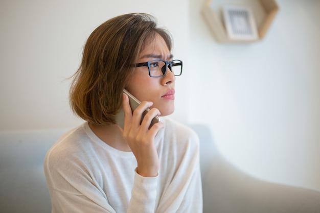 Mujer tensada que pide en smartphone en el sofá en casa