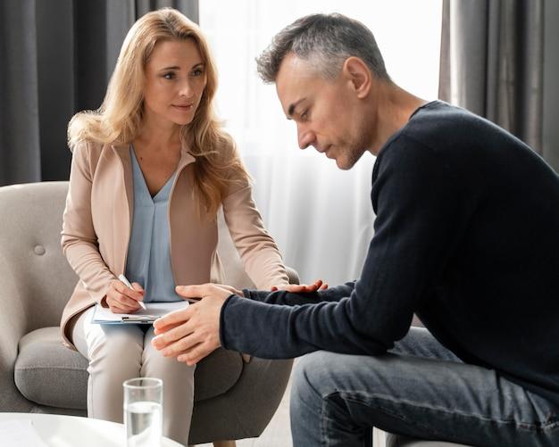 Mujer terapeuta de tiro medio reconfortante paciente
