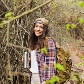 Mujer con termo en el bosque