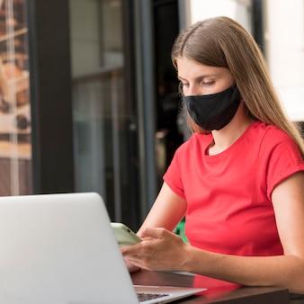 Mujer en terraza trabajando con mascarilla