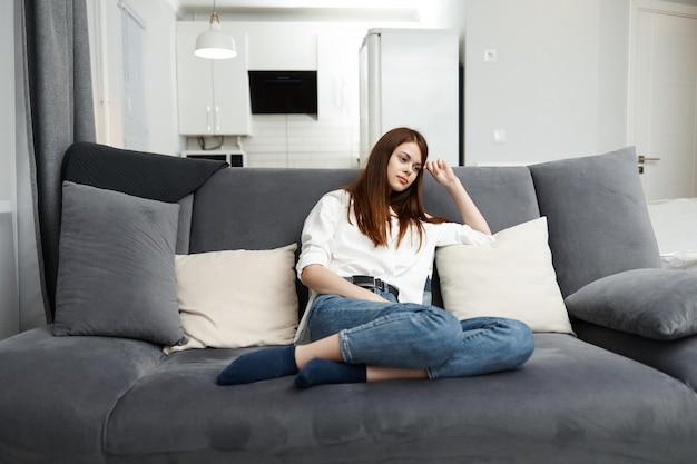 Mujer en el tiempo libre descansando en el sofá casa interior