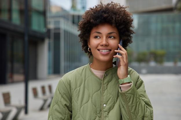 La mujer tiene conversación telefónica se encuentra afuera en el entorno urbano satisfecho con las tarifas en roaming viste chaqueta