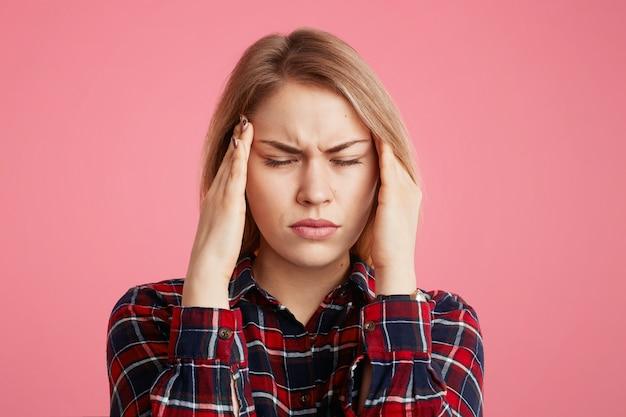 La mujer tiene dolor de cabeza, mantiene las manos en las sienes, cierra los ojos al sentir un dolor terrible, trabajar demasiado y fatiga