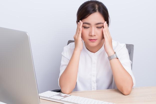La mujer tiene dolor de cabeza por el trabajo.