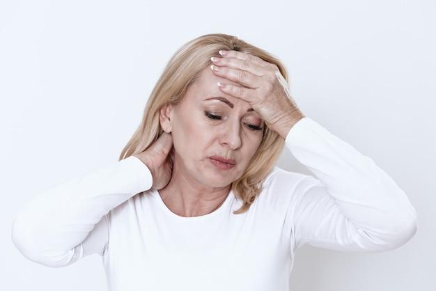 Una mujer tiene dolor de cuello. ella se siente mal.