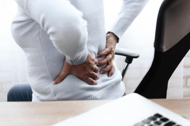 La mujer tiene dolor en la espalda. ella se siente mal.
