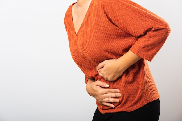 La mujer tiene dolor de estómago con las manos en el abdomen, parte del cuerpo