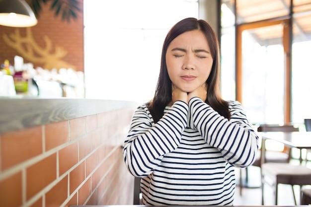 La mujer tiene dolor de garganta en el café