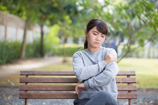 La mujer tiene dolor de hombro en el parque