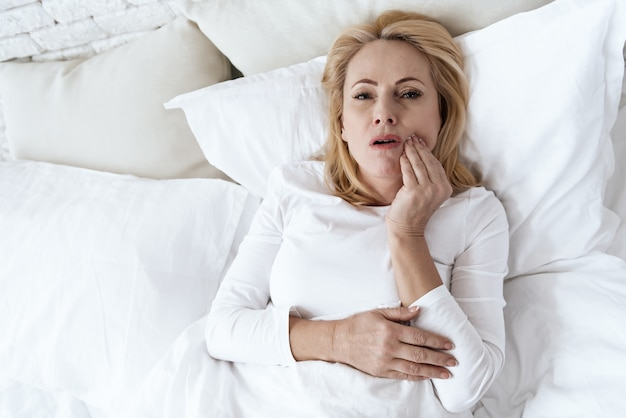 La mujer tiene un dolor de muelas. ella se siente mal. duele.